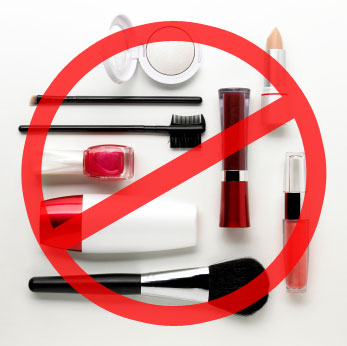 Various makeup items and brushes on a white background stamped with a red circle with a line through it
