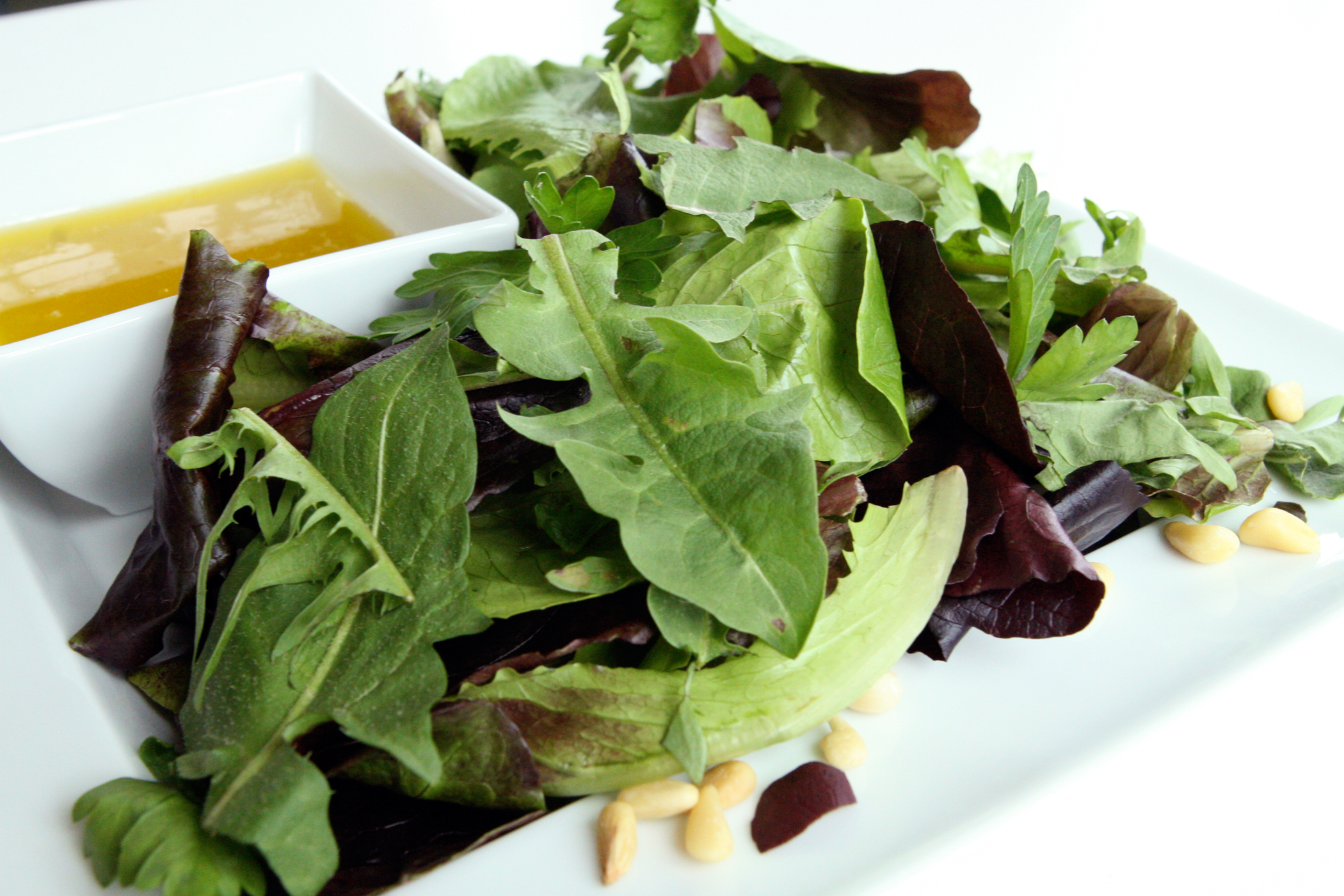 Close-up of a salad dish with nuts and olive oil in a small dip dish
