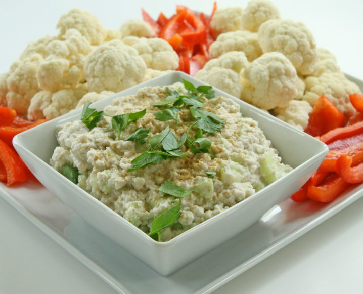 Close-up of a white plate with cauliflower and red peppers and a small dish with cauliflower dip