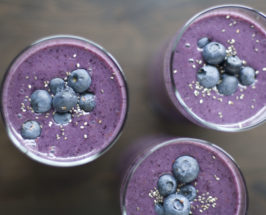 Three glasses of a blueberry shake made from Alejandro Junger recipes