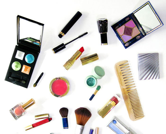 Makeup items and brushes on a white background, including lipsticks, mascaras, eyeshadow palettes and more