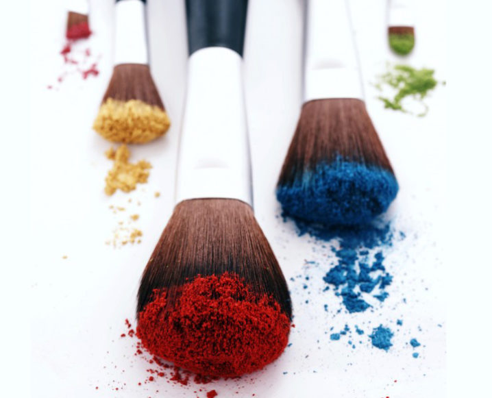 Close-up of 5 different makeup brushes with different colored powders on their bristles