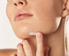 Close-up of a woman's face nose down and her neck, applying face cream on a chin