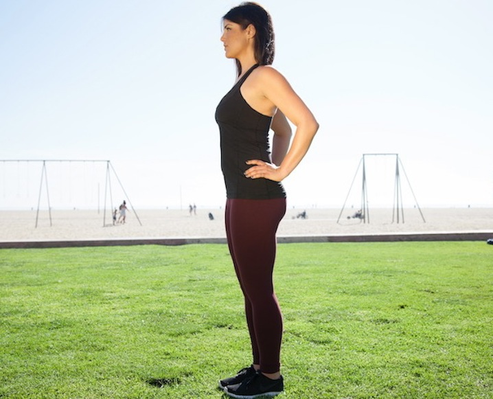 Woman in workout clothes on a grass field with the beach in the background