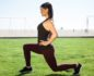 Woman doing lunges in the grass with the beach in the background