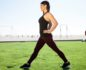 Woman in workout clothes doing lunge steps in the grass