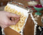 Hand decorating the roof of a gingerbread house with banana slices