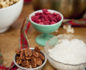 Small bowl of pecans, glass of raspberries and large bowl of coconut flakes on a wooden table