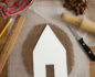 A cardboard template for house-shaped cookies on a sheet of baking paper, with a pencil, ruler, rolling pin and knife