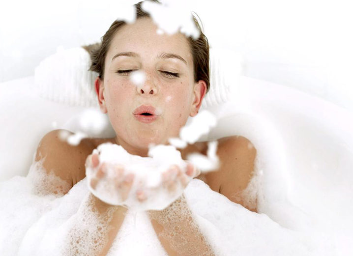 A woman in a bathtub covered in and blowing soap bubbles