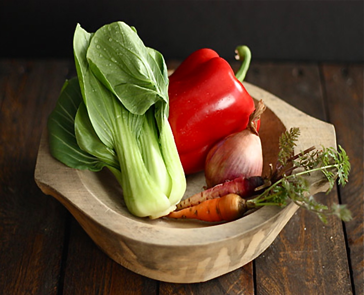 A wooden vegetable bowl with lettuce, carrots, onion and red pepper on a wooden table