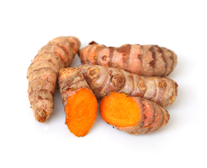 Four pieces of turmeric on a white background, one of which is cut in half