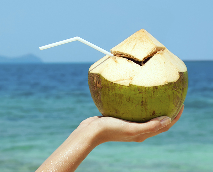 Hand holding a green coconut carved at the top and with a straw in it, in front of a scenic ocean background