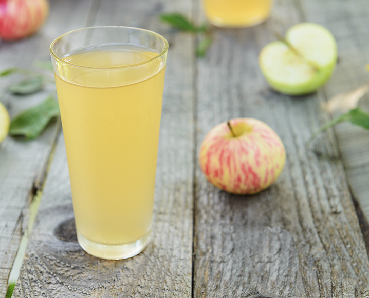 Tall glass of apple cider vinegar surrounded by apples on a wooden table