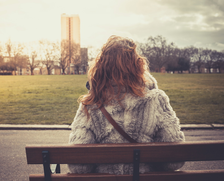 Back of a woman sitting on a park bench looking out at the view