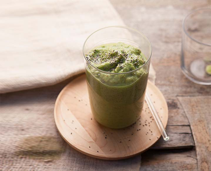 Glass of green juice on a wooden coaster with a small plastic straw on a blurred wooden table background