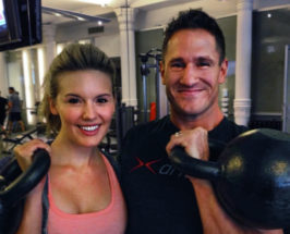 Medium shot of a woman and celeb trainer Don Saladino in a gym background holding weights