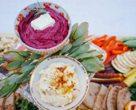 Two bowls of hummus, one from neon beets and one regular on a blurred background of snacks spread