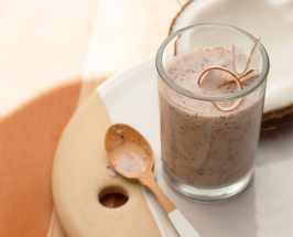 A glass of coconut-based smoothie with half a coconut in the background and a wooden teaspoon next to it