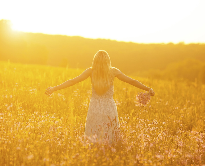Woman with her back turned in a sunbathed field of lavender