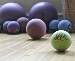 Wooden floor with yoga tune up balls of different colors and sizes