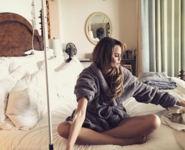A woman in a bathrobe on a bed with a Myers cocktail IV in her arm