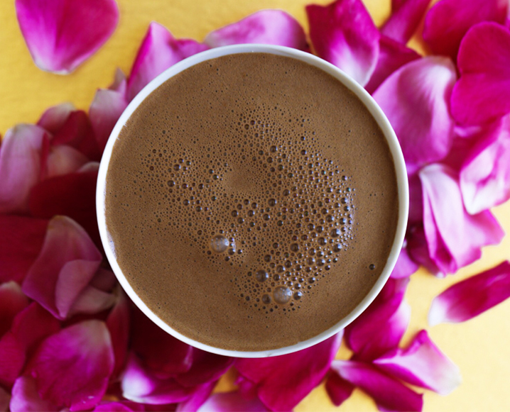 Aerial view of a cup of chocolate drink on a background of pink flower petals