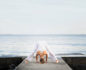 Woman in a head down crown chakra yoga pose on a pier