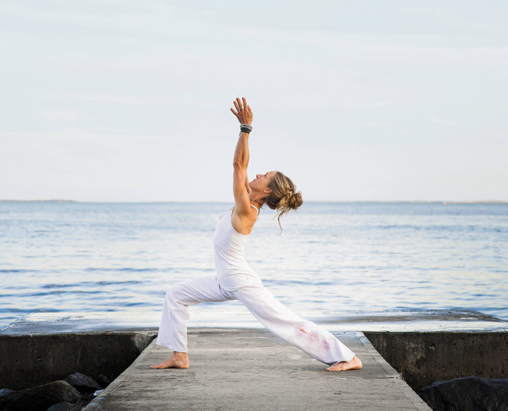 Woman in crown chakra yoga pose on a pier with an ocean background