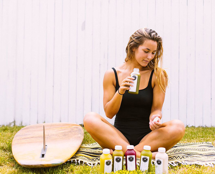 Professional surfer Maddie Peterson sitting on a blanket in the grass with a surfboard next to her and drinking Pressed Juicery juice
