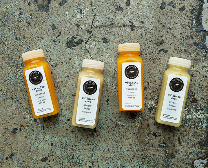 Two bottles of Pressed Juicery vitality shot and two bottles of wellness shot on a stone background