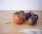 Eight small tomatoes with purple shades on a wooden surface
