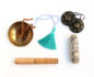A mala in a singing bowl with sage and Tingsha bells next to it
