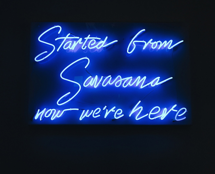 Blue neon sign with Started from Savasana now we're here on a black background
