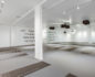 Long shot of a yoga studio with speakers on the ceiling, mirror walls and yoga mats on the floor