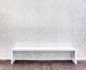 White wooden bench against a wallpapered art deco wall