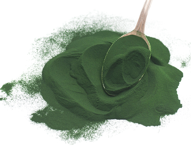 Green powder spread on a white background with a teaspoon of scooped powder