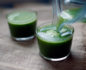 Two glasses of alkalizing green juice on a linen tablecloth with a pitcher pouring into one of the glasses