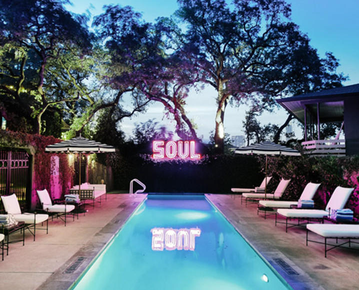 Hotel Saint Cecilia's pool in Austin, TX with tall trees in the background and the word SOUL in neon pink light