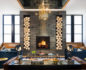 Medium shot of the Hotel Van Zandt lounge with an open log fireplace, leather chairs, and glass coffee tables