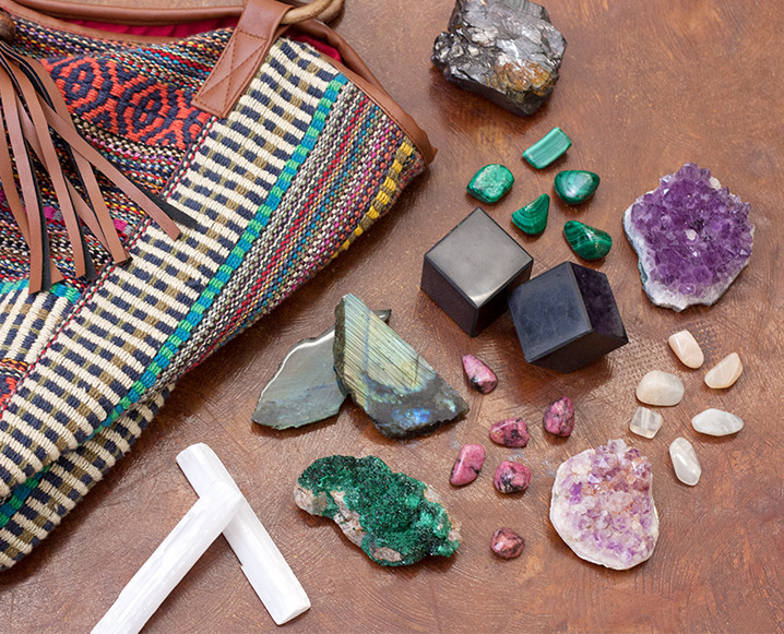 Partial view of a colorful shoulder bag with 11 different crystals and stones for travel next to it