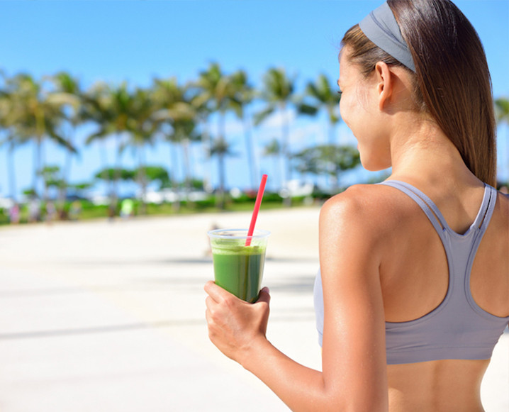 Back shot of a woman in workout clothes on a beach boardwalk with a glass of green juice in hand