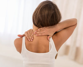 A woman's back with her hands trying to massage her shoulders and neck against fibromyalgia pain