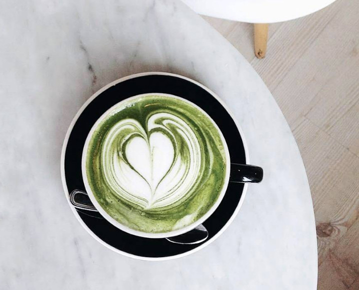 Aerial view of a cup of matcha latte with a heart shape top foam and a small teaspoon on the saucer