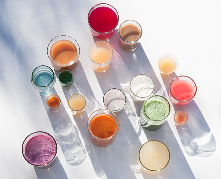 Aerial shot of 14 glasses of juice with different colors and in different sizes
