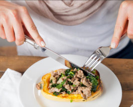 Close-up of a pumpkin dish with meat and kale and someone cutting a bite to eat with knife and fork