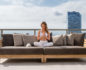 Long shot of a high-level balcony with a large sofa and a woman meditating on it