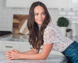Woman wearing jeans and white lace shirt leaning forward and resting on a marble countertop in a kitchen