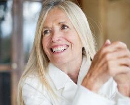 Medium shot of Mimi Kirk, smiling, on a blurred background