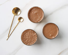 three cups of superfood latte on marble counter with gold spoons